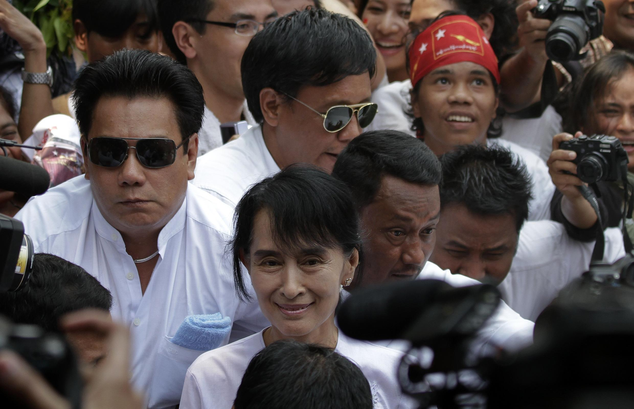 Myanmar's pro-democracy leader Aung San Suu Kyi makes her way trough the crowd as she arrives to the office of NLD in Yangon