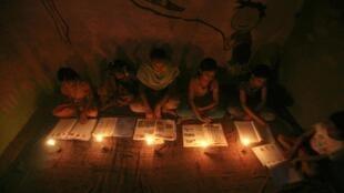 Des enfants dans une école coranique de New Delhi, lisant à la lumière de bougies le 30 juillet 2012.