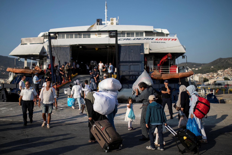 Des migrants afghans montent à bord d'un bateau qui les transférera sur le continent, à Mytilene, sur l'île de Lesbos, le 2 septembre 2019.