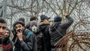 Varios migrantes tratan de derribar una alambrada durante unos enfrentamientos con la policía griega por intentar entrar en Grecia, el 4 de marzo de 2020 en la localidad fronteriza de Edirne, en Turquía