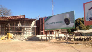 'Welcome to Kanilai' billboard with photo of Jammeh, next to construction site.
