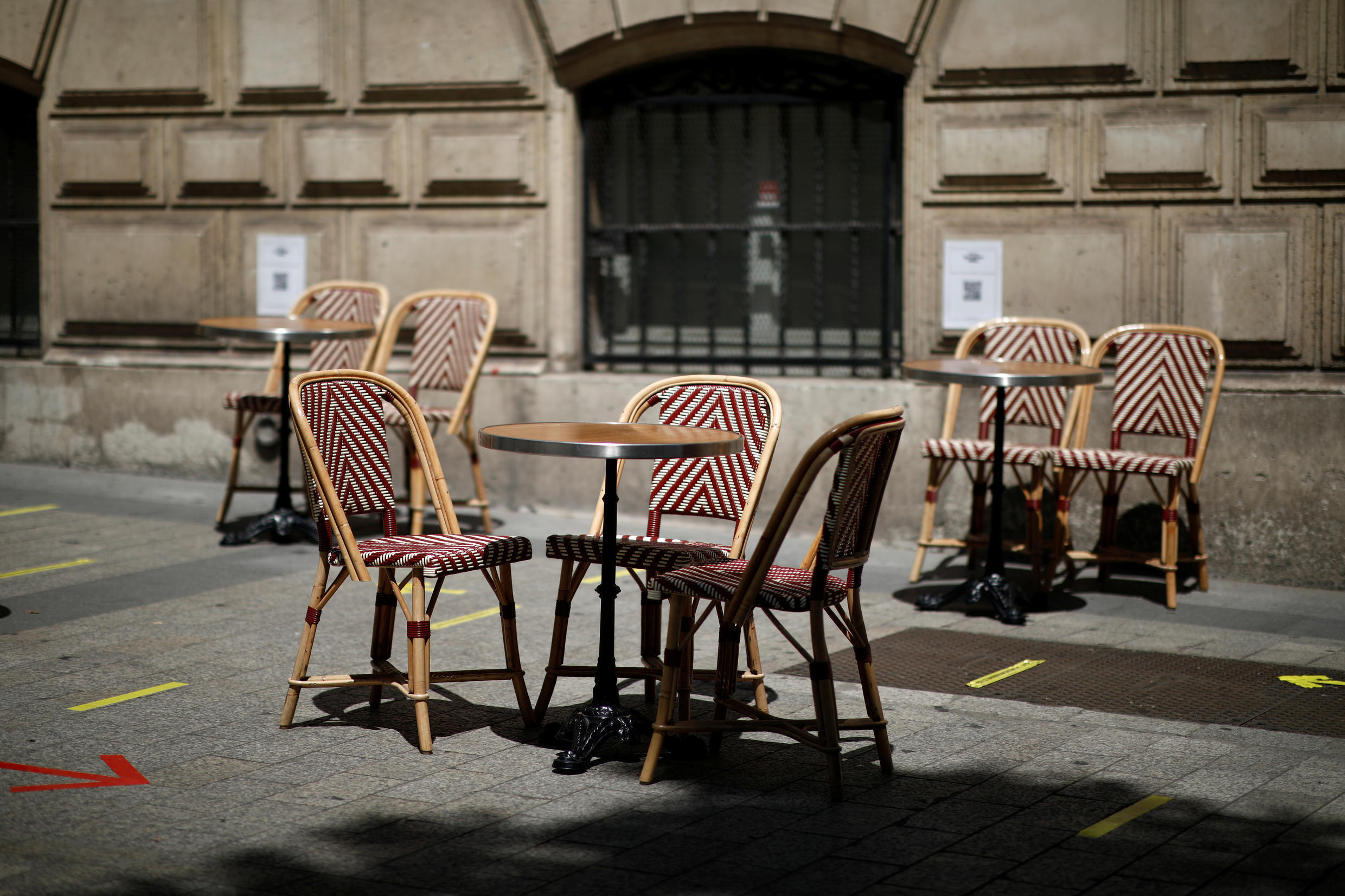 Social distancing signs are seen on the pavement near tables and chairs on a terrace of a restaurant in Paris as restaurants and cafes reopen in Paris on 2 June, 2020.