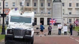 Un furgón policial permanece estacionado cerca de un pequeño grupo de unionistas que se manifiestan frente al Parlamento de Irlanda del Norte, el 8 de abril de 2021 en Belfast
