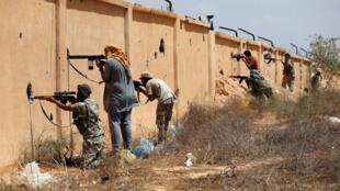 Des combattants libyens alliés au gouvernement soutenu par l'ONU tirent sur des éléments du groupe terroriste Etat islamique, à Syrte, le 15 juillet 2016.
