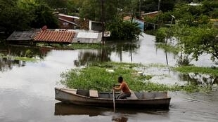 Um homem rema em uma rua inundada pelas fortes chuvas que provocaram a inchente do rio Paraguai, na periferia de Assunção.