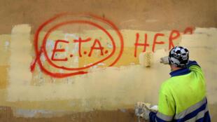 """Um operário  pinta  numa  parede da cidade basca de Guernica  :"""" ETA , nós  estamos convosco"""". 21 de Outubro  de 2011.(Fotografia  de arquivo).                                                                     Foto de archivo del 21 de octubre de 2011."""