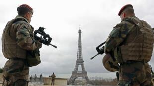 Des militaires patrouillent dans le secteur de la Tour Eiffel, à Paris, dans le cadre de l'état d'urgence, le 30 mars 2016.