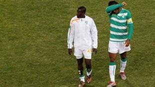 Didier Drogba e Emmanuel Eboué deixam o campo após derrota.