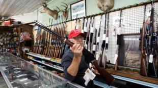Dans une armurerie de Wildwood en Floride, le vendeur propose un fusil de chasse à un client, le 15 octobre 2020 (image d'illustration).