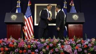 le président Obama serrant la main de son homologue salvadorien Funes à l'issue de leur entretien au Palais présidentiel de San Salvador, le 22 mars 2011