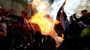 Des manifestants brûlent le drapeau israélien pendant la manifestation contre la décision de Donald Trump de reconnaitre Jérusalem comme capitale d'Israël. Amman, le 8 décembre 2017.