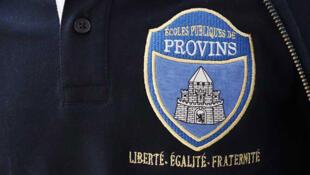Ecusson figurant sur l'uniforme scolaire bleu marine et bleu ciel à Provins, en Seine-et-Marne.