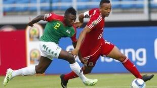 Mchezaji wa Burkina Faso Steeve Yago akikabiliana na mchezaji wa Equatorial Guinea Emilio Nsue Lopez.