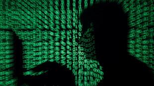 Un hombre sostiene una computadora al mismo tiempo que se proyecta un código digital.