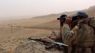 Syrian soldiers watch Islamic State fighters in Palmyra