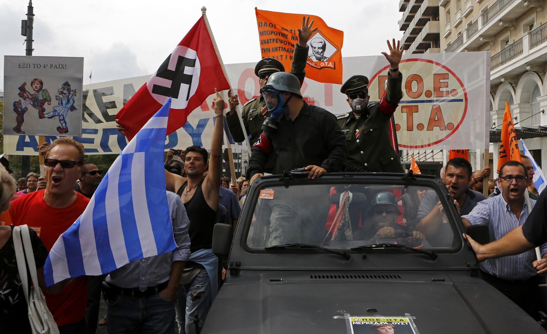 Manifestantes gregos protestam com bandeiras nazistas no centro de Atenas contra a visita da chanceler alemã, Angela Merkel.