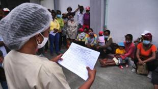 Madagascar: la représentante de Médecins du Monde annonce aux parents la date de l'intervention pour la chirurgie de fente labiopalatine de leur enfant et donne les dernières recommandations avant le jour J (février 2021).