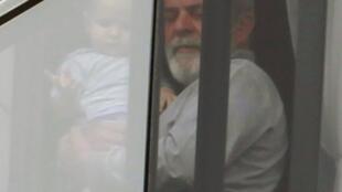O ex-presidente Lula segura seu neto Pedro no colo, na janela de seu apartamento em São Bernardo do Campo, neste domingo.