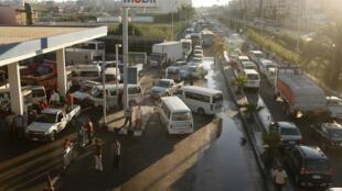 Des conducteurs attendent à côté de leurs véhicule, devant une station, à Alexandrie, le 24 juin 2013