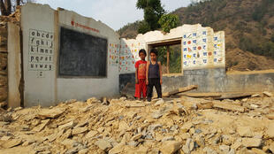 孩童站在一座425地震后校园废墟前面。