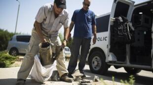 Служащий гражданской обороны Израиля собирает осколки ракеты, выпущенной из Газы по полесению Кфар Маймун 30/06/2014