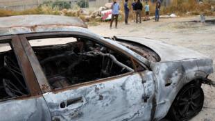Un grupo de israelíes se reúnen cerca de un automóvil quemado durante la reciente violencia intracomunal entre árabes y judíos israelíes en la ciudad árabe israelí de Lod, cerca de Tel Aviv, el 23 de mayo de 2021.