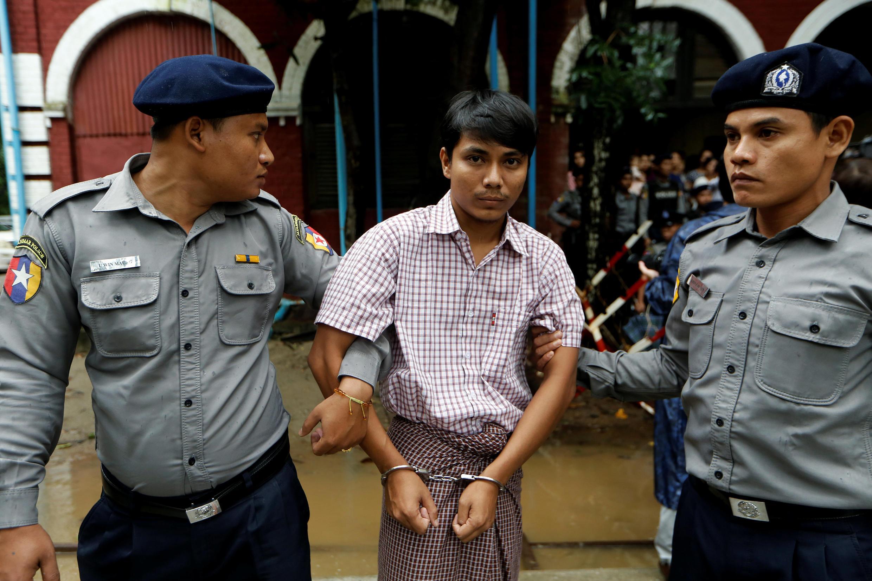 Nhà báo Kyaw Soe Oo (G) làm việc cho hãng tin Reuters sau khi rời tòa án Insein tại Rangun, Miến Điện ngày 09/07/2018.