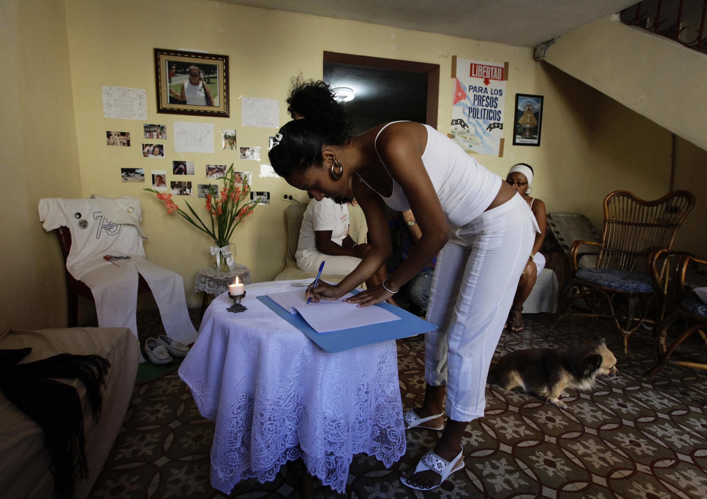 Pessoas assinam livro de visitas em funeral de opositor do regime cubano, morto após greve de fome.