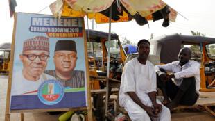 Des Nigérians devant des affiches de campagne du président en exercice Muhammadu Buhari, après l'annonce du report de l'élection prévue le 16 février, à Yola, dans l'Etat d'Adamawa.
