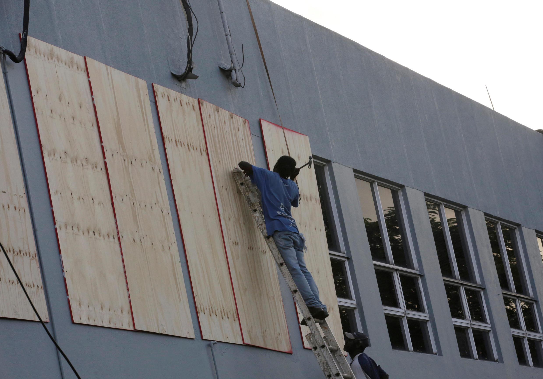 Trabajadores cubriendo las ventanas de un edificio en Kingston, Jamaica, antes de la llegada del huracán Matthew.