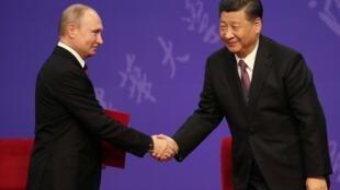 Tổng thống Nga Vladimir Putin (T) bắt tay chủ tịch Trung Quốc Tập Cận Bình tại một buổi lễ ở trường đại học Thanh Hoa, Bắc Kinh, ngày 26/04/2019