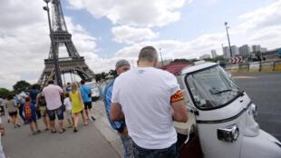 Un policier procède à un contrôle auprès d'un chauffeur de tuk-tuk devant la Tour Eiffel.