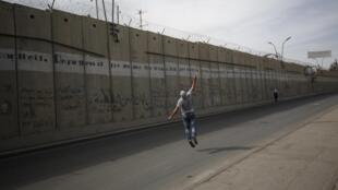 22 octobre 2015, un Palestinien jette des pierres par-dessus le mur dont la largeur peut dépasser à certains endroits les 50 mètres.