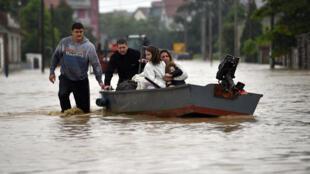 Une famille est évacuée par bateau dans la ville inondée de Obrenovac, à 40 kilomètres à l'ouest de Belgrade, le 16 mai 2014.