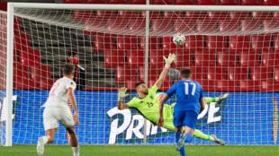 Le gardien espagnol Unai Simon battu sur penalty par Anastasios Bakasetas (#17) pour l'égalisation de la Grèce au stade de Los Carmenes à Grenade, le 25 mars 2021
