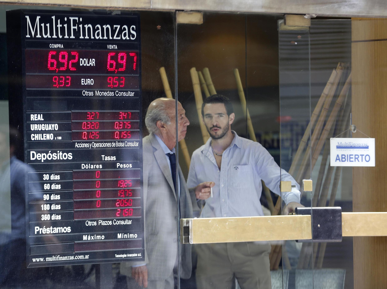 Deux analystes se tiennent près d'un panneau indiquant les valeurs du peso argentin et du dollar américain.