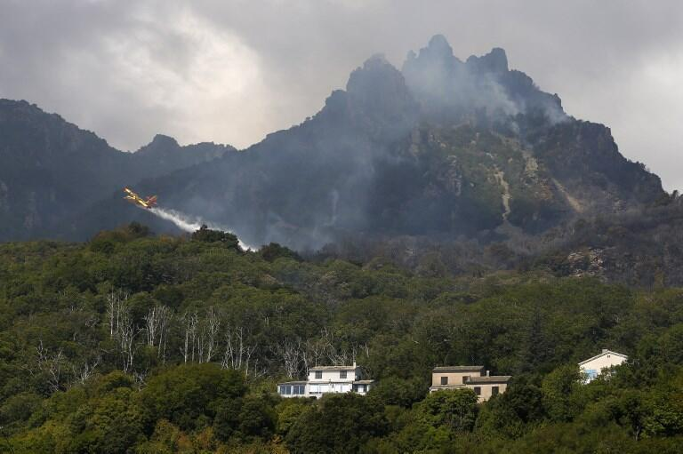 A firefighting Canadair drops water on a hill above Sisc Corsica this weekend