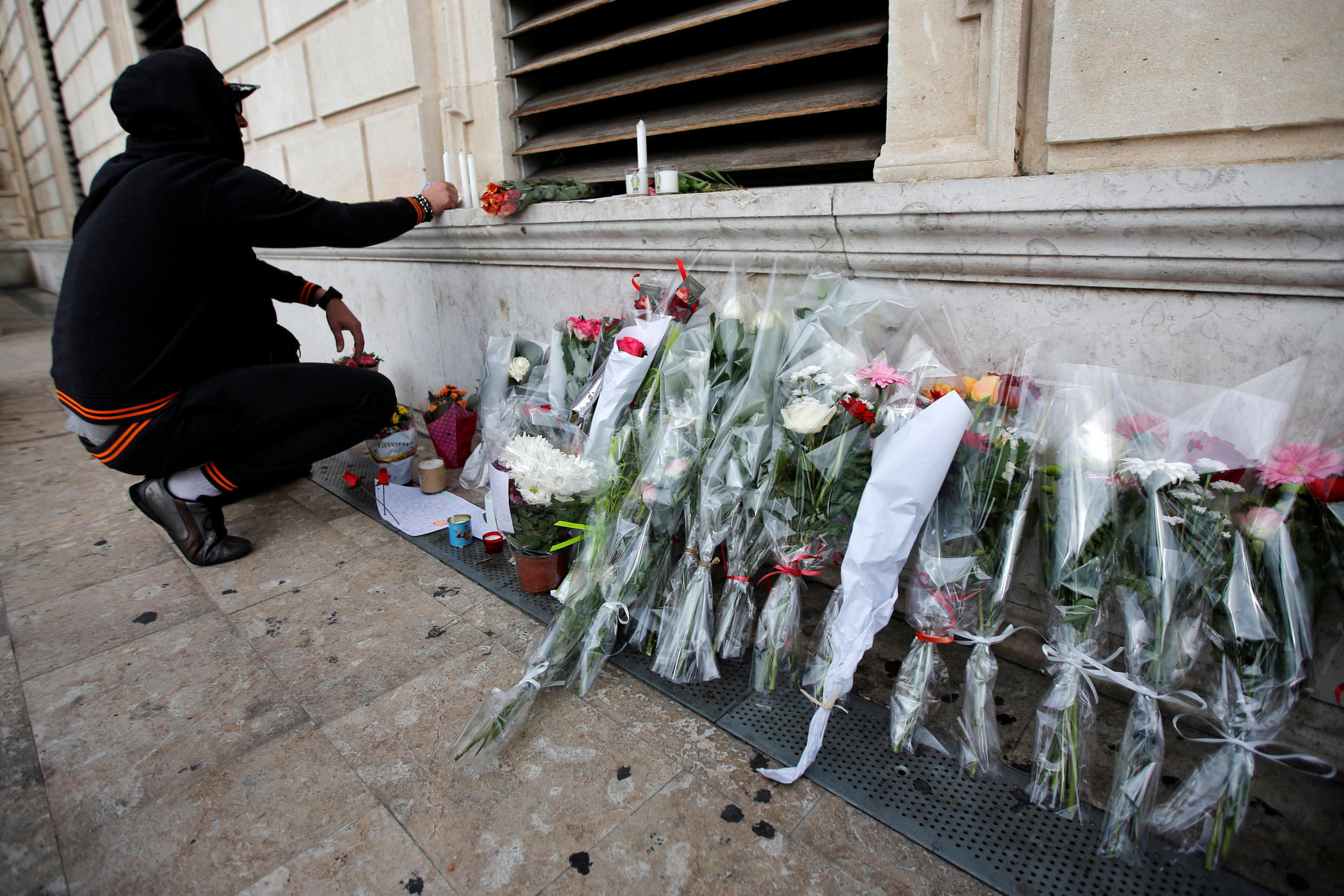 A man installs candles in tribute to the two women who were stabbed to death by a knife attack at the main train station in Marseille A man installs candles in tribute to the two women who were stabbed to death Sunday at the main train station
