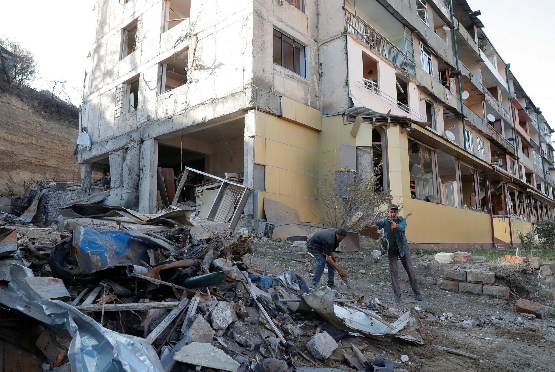 Des habitants regardent les débris d'un bâtiment détruit par les conflits dans le Haut-Karabakh, dans la capitale Stepanakert, le 19 octobre 2020.