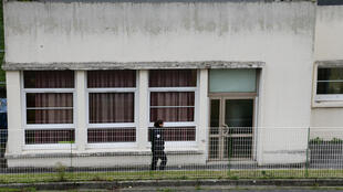 A police officer in front of the school in Aubervilliers where a teacher was attacked, 14 December 2015