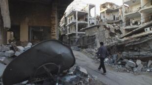 Sírio caminha em rua de Homs danificada por bombardeios do exército sírio.