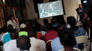 Des Haïtiens regardent une retransmission télévisée des excuses de Ban Ki-moon pour le choléra en Haïti, le 1er décembre 2016.