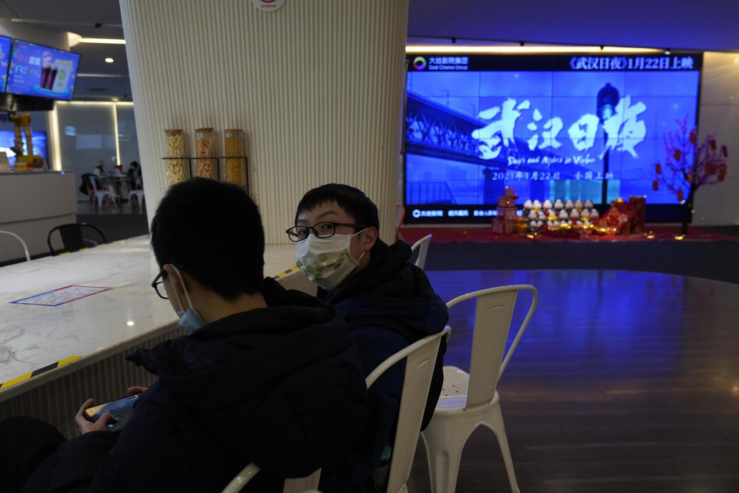 "Youths wearing masks to protect from the coronavirus chat near a screen showing a trailer for the film ""Days and Nights in Wuhan"" in a cineplex in Wuhan in central China's Hubei province on Friday, Jan. 22, 2021. China is rolling out the state-backed film praising Wuhan ahead of the anniversary of the 76-day lockdown in the central Chinese city where the coronavirus was first detected."