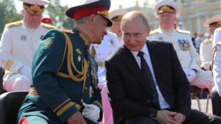 Tổng thống Nga Vladimir Putin (P) và bộ trưởng Quốc phòng Serguei Shoigu tham dự lễ diễu binh nhân ngày Hải Quân Nga, Saint Petersburg, ngày 29/07/2018