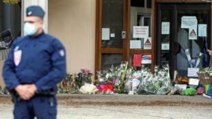 Flores e homenagens em frente à escola em Conflans-Sainte-Honorine, na França, onde um professor foi decapitado na sexta-feira (16) de outubro de 2020.