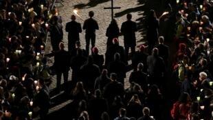 Fieles llevando la cruz en el tradicional viacrucis de Viernes Santo, en el coliseo romano.