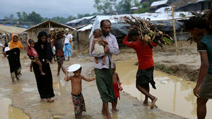 Rohingya refugees walk along the Balukhali refugee camp after the rain in Cox's Bazar, Bangladesh, 6 October, 2017.
