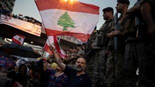 Un manifestant brandit le drapeau libanais face à l'armée durant un défilé à Jal el-Dib, le 23 octobre.