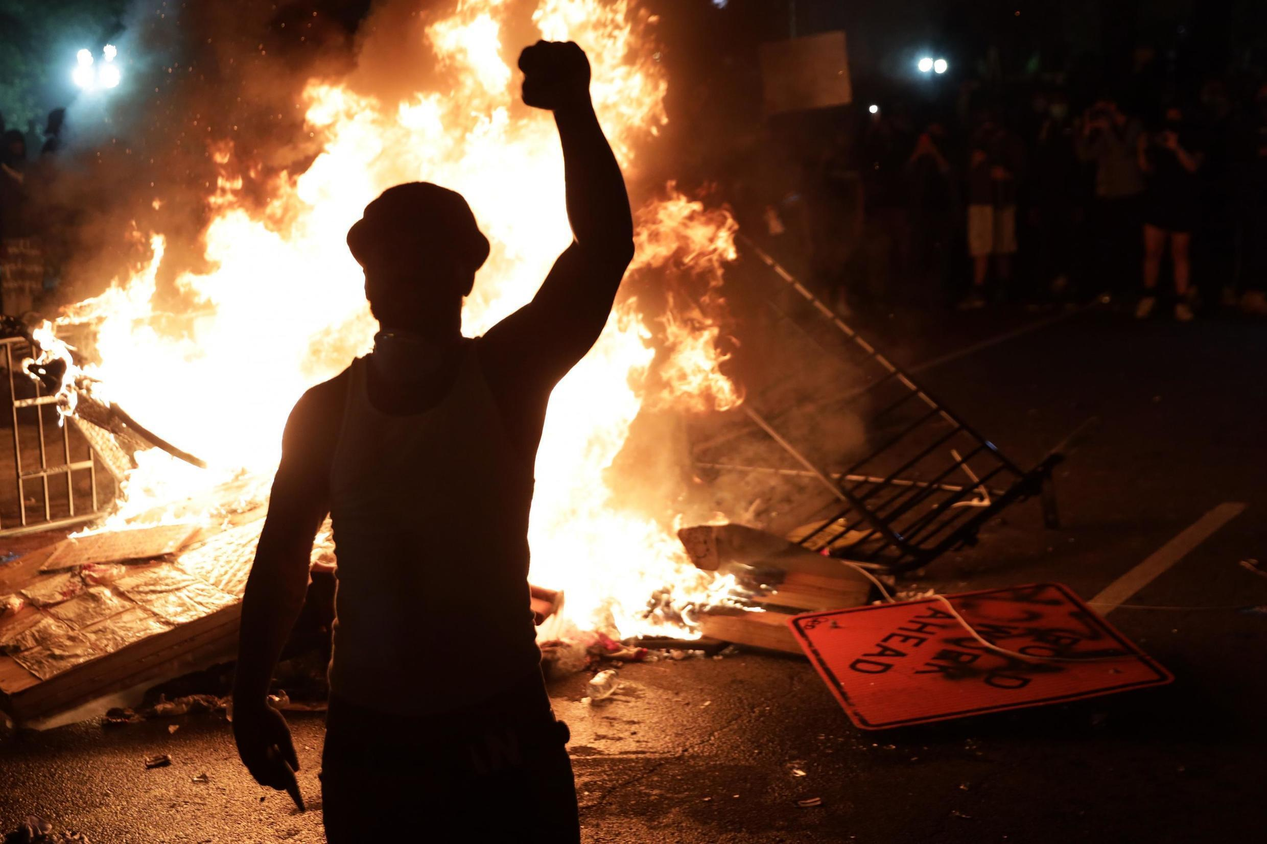 A protester raises a fist near a fire during a demonstration outside the White House over the death of George Floyd, a black man, at the hands of Minneapolis Police on 25 May.