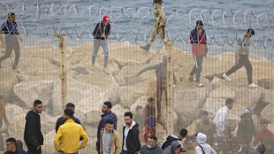 Migrants slip through a fence in the northern town of Fnideq in an attempt to cross the border from Morocco to Spain's North African enclave of Ceuta